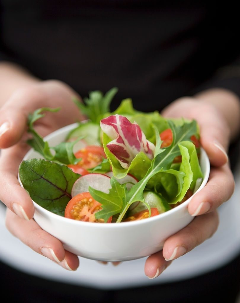 Hands Holding A Small White Ball With Mixed Salad