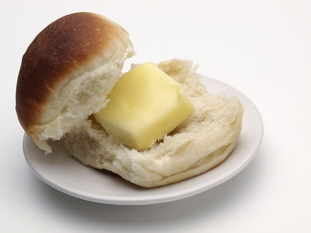 """single White Dinner Roll On Side Plate, Split Open With Butter Pat."""